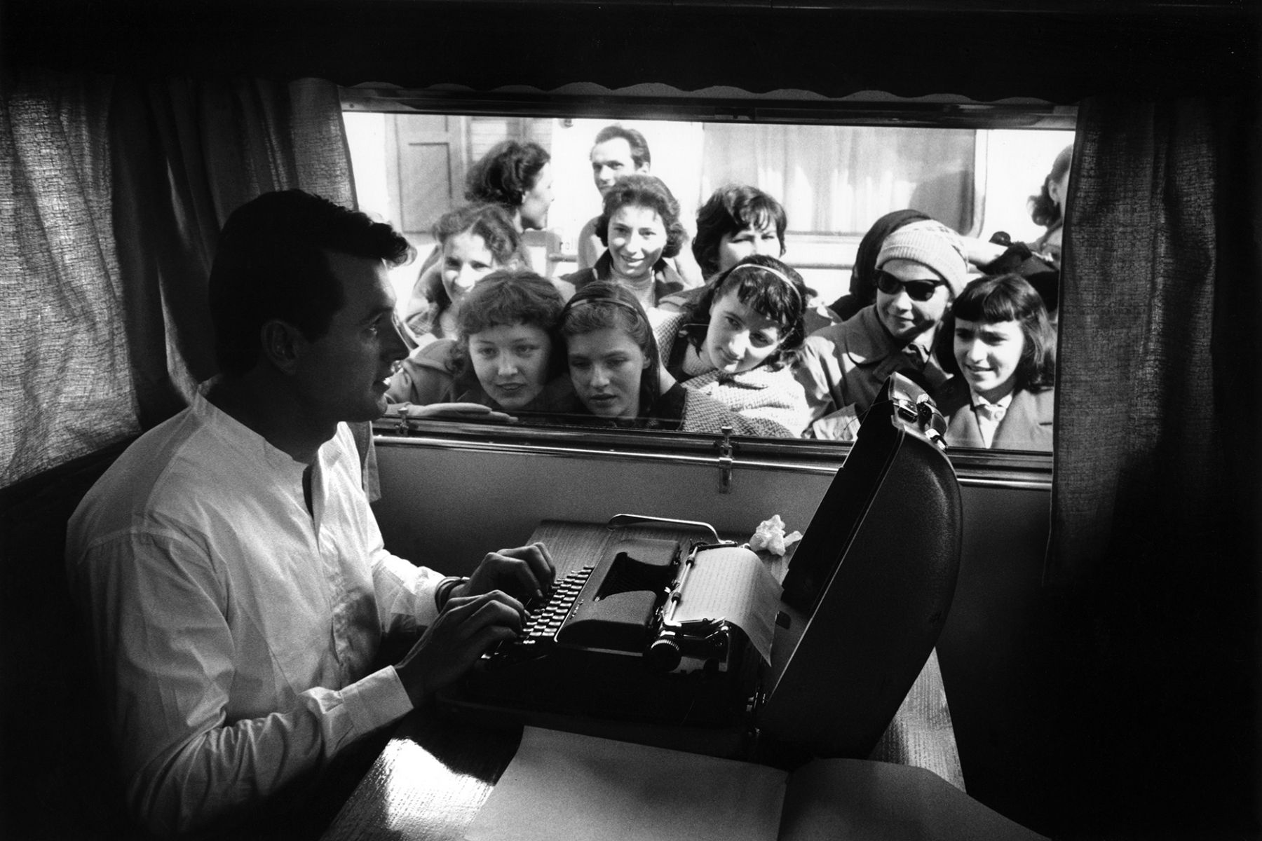 Rock Hudson trying to type in his trailer, but the fans are a bit distracting. On location in Grado, Italy for A Farewell to Arms, 1957.