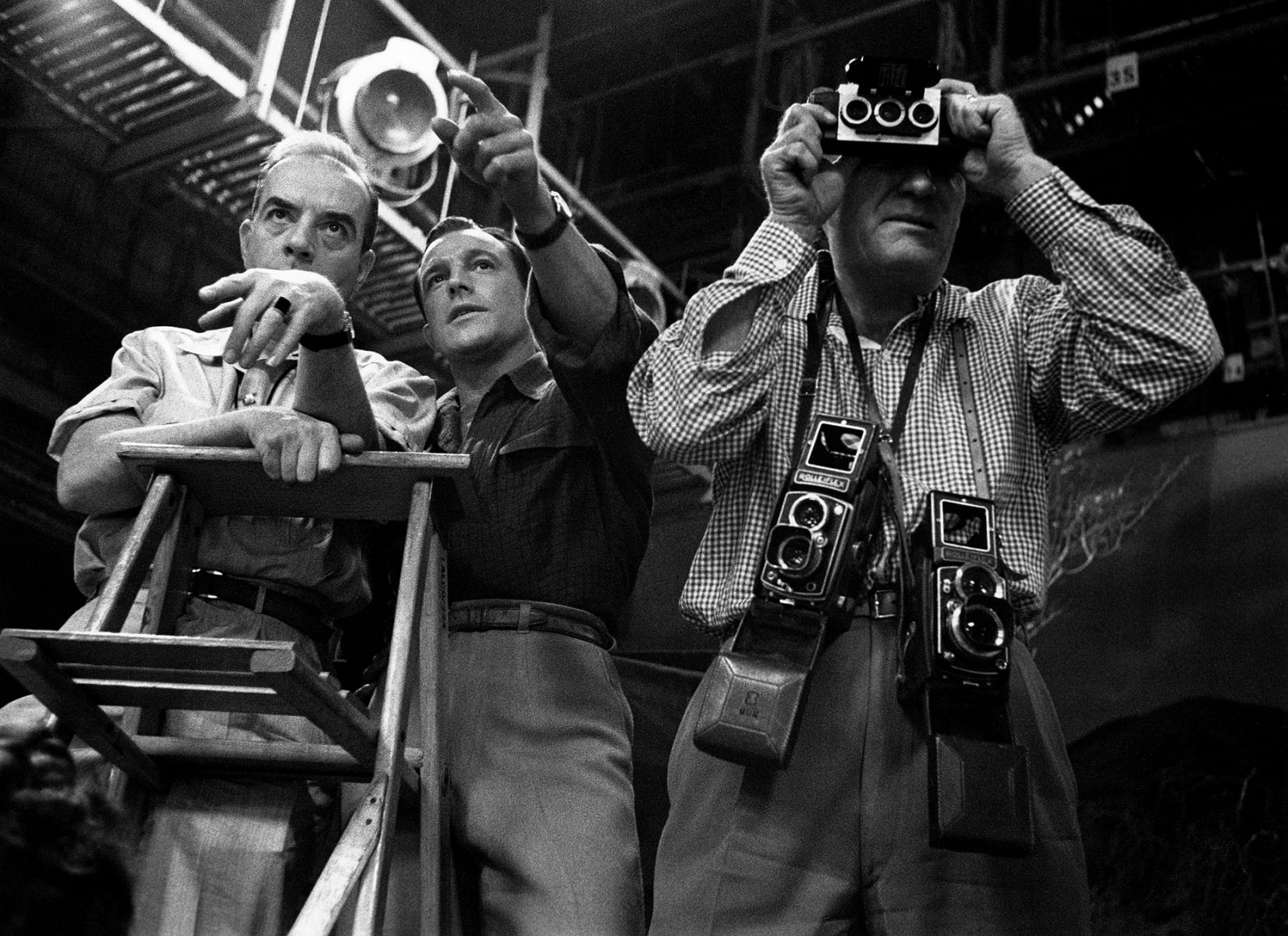 Vincente Minnelli and Gene Kelly discuss the placement of dancers on Brigadoon while MGM stills man Eric Carpenter takes a 3D picture for the directors, 1954.