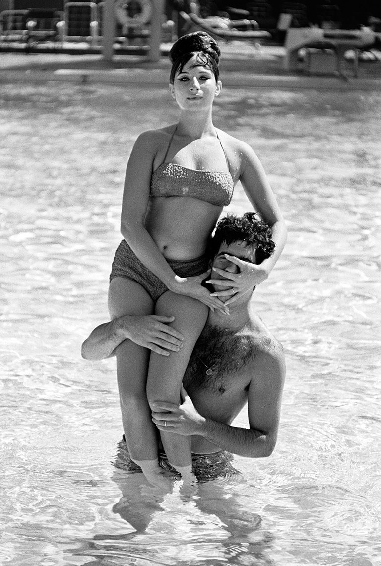 Barbra Streisand sitting on her husband Elliott Gould's shoulders in the Beverly Hills Hotel pool, 1963.