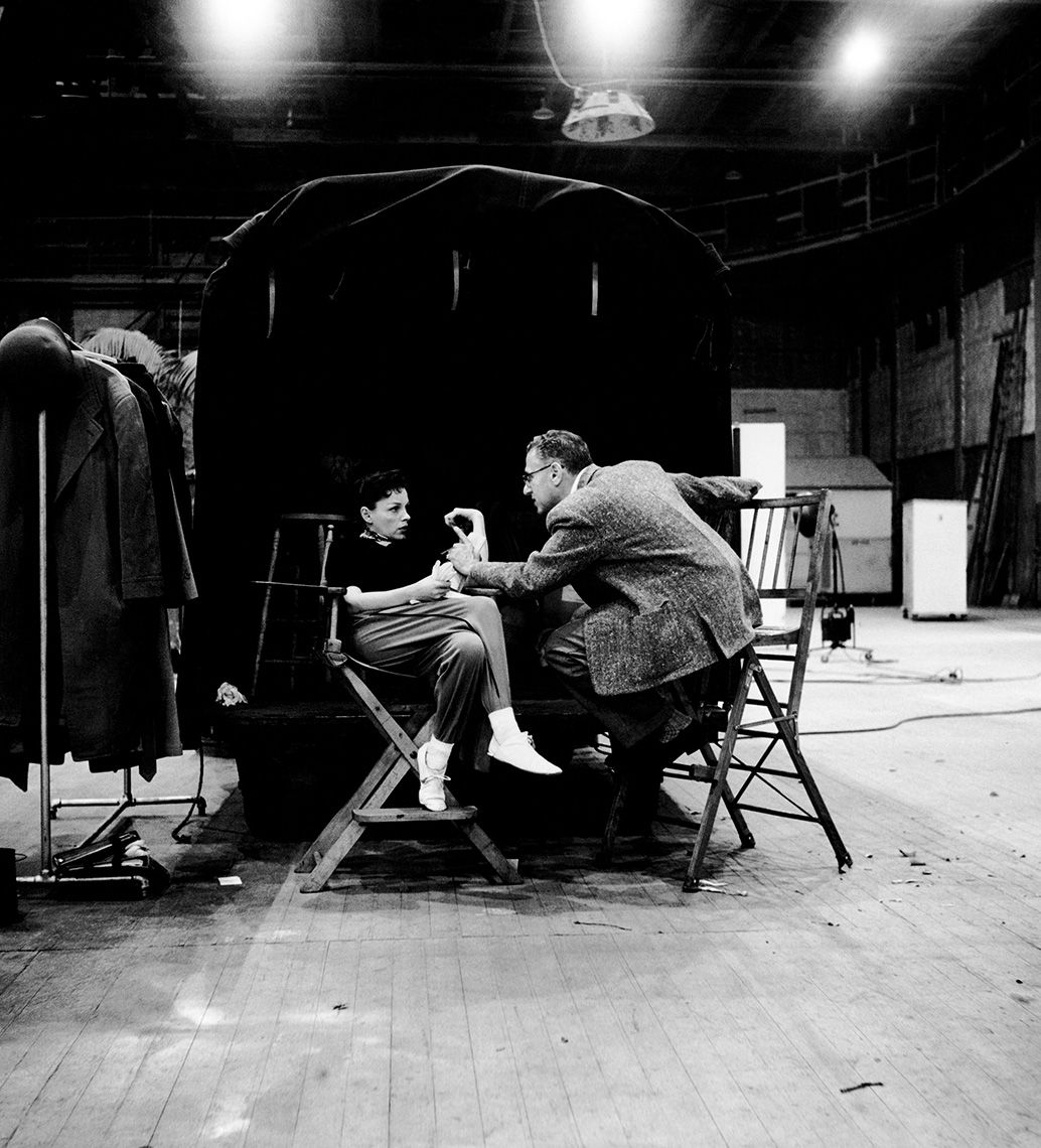 """Director George Cukor gives Judy Garland the """"word"""" on a deserted sound stage during A Star Is Born, 1954."""