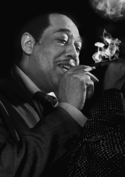 Duke Ellington lighting Gene Norman's cigar at the Shrine Auditorium in Los Angeles, 1950.