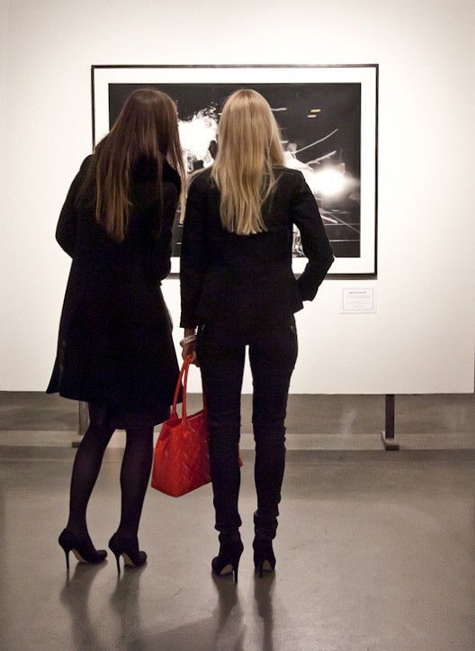 Women looking at photograph in a gallery